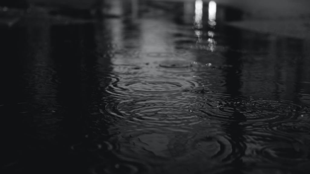 black and white photo of rain and puddles